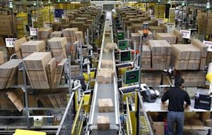 Workers pack boxes at Amazon's logistics centre in Graben