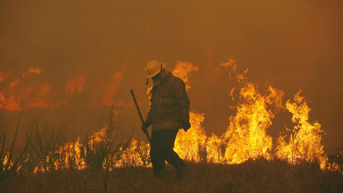 Firefighters from around the state battle a large wildfire on Highway 71 near Smithville, Texas, Monday, Sep. 5, 2011.  A roaring wildfire raced unchecked Monday through rain-starved farm and ranchland in Texas, destroying nearly 500 homes during a rapid advance fanned in part by howling winds from the remnants of Tropical Storm Lee. (AP Photo/Erich Schlegel)