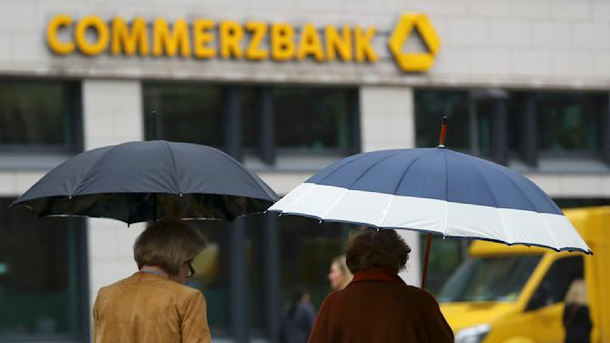 People with umbrellas walk past a Commerzbank branch in Frankfurt
