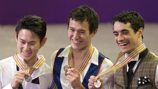 Gold medalist Patrick Chan, center, of Canada, flanked by silver medalist Dennis Ten, left, of Kazakstan, and bronze medalist Javier Fernandez, of Spain, show off their medals during the flower ceremony in the men's competition at the World Figure Skating Championships Friday, March 15, 2013 in London, Ontario. AP Photo/The Canadian Press, Frank Gunn)