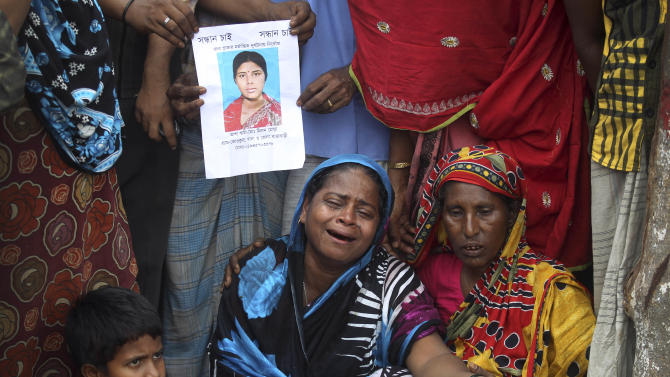 "Women cry as others hold a portrait of her missing relative at the site of the collapsed garment factory building on Tuesday, April 30, 2013 in Savar, near Dhaka, Bangladesh.   A top Bangladesh court on Tuesday ordered the government to ""immediately"" confiscate the property of a collapsed building's owner, as thousands of protesters demanding death penalty for the man clashed with police, leaving 100 people injured.  (AP Photo/Wong Maye-E)"