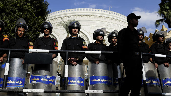 """Egyptian riot policemen guard a gate of the presidential palace, background, amid ongoing protests, in Cairo, Egypt, Saturday, Dec. 8, 2012. Egypt's military has warned of 'disastrous consequences' if the political crisis gripping the country is not resolved through dialogue. """" (AP Photo/Hassan Ammar)"""