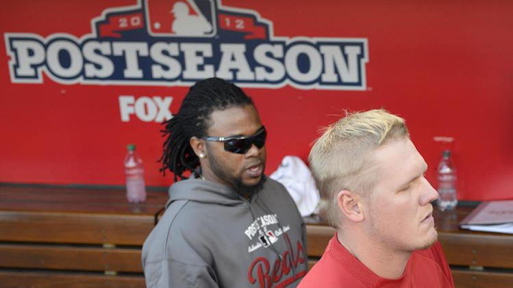 Cincinnati Reds starting pitcher Mat Latos, right, leaves the dugout with pitcher Johnny Cueto after the Giants defeated the Reds 6-4 in Game 5 of the National League division baseball series, Thursday, Oct. 11, 2012, in Cincinnati.  The Giants won the final three games, all in Cincinnati, and advanced to the NL championship series. (AP Photo/Michael Keating)