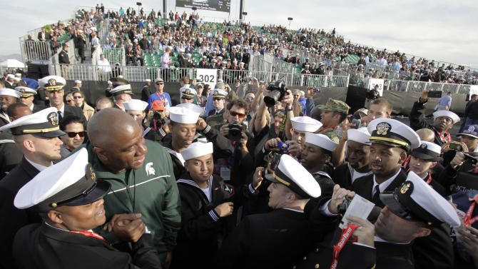 Former Michigan State basketball player and NBA great Magic Johnson poses with members of the Navy as he arrives for the Carrier Classic NCAA college basketball game aboard the USS Carl Vinson, Friday, Nov. 11, 2011, in Coronado, Calif.  Michigan State will face No. 1 North Carolina in the inaugural game. (AP Photo/Gregory Bull)