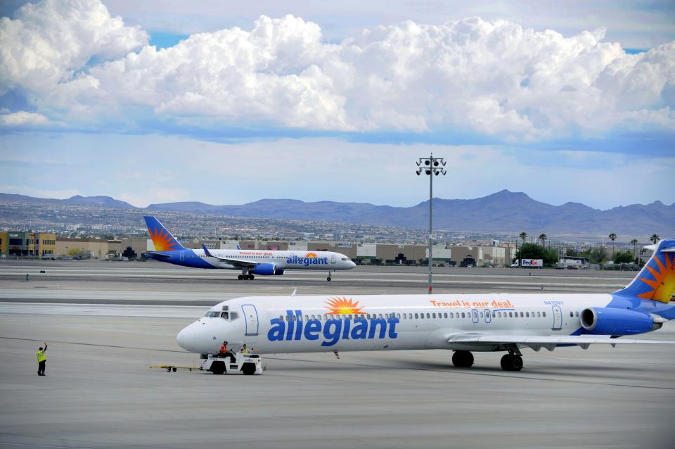 In this Thursday, May 9, 2013, photo, two Allegiant Air jets taxi at McCarran International Airport in Las Vegas. While other U.S. airlines have struggled with the ups and downs of the economy and oil prices, tiny Allegiant Air has been profitable for 10 straight years. (AP Photo/David Becker)