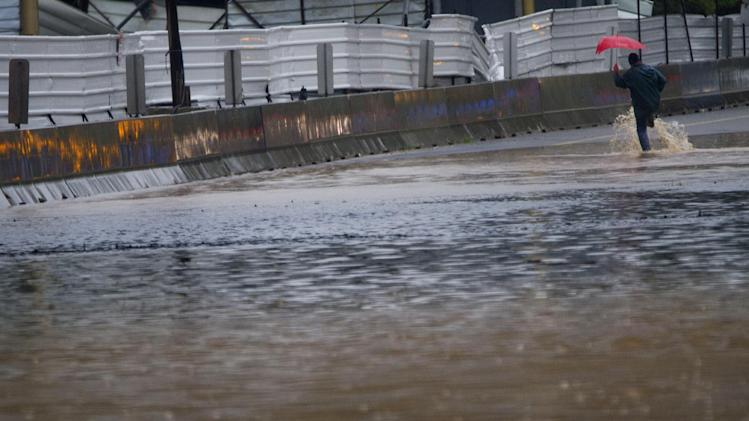 A person crosses the blocked Ayalon freeway in Tel Aviv, Israel,Tuesday, Jan. 8, 2013. Heavy rains flooded Tel Aviv. (AP Photo/Ariel Schalit)