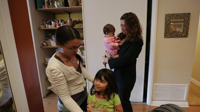 In this Sept. 26, 2012 picture, Sabina Widmann, right, holds her baby girl Stella while domestic worker Alicia Wotherspoon, left, helps her daughter Luna with a glass of water before work at their home in San Diego. (AP Photo/Gregory Bull)