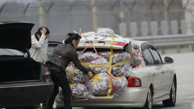 A South Korean worker, left, who arrives with electronic products from North Korea's Kaesong, is helped by a South Korean woman who greeted him, after returning from the North at the customs, immigration and quarantine office near the border village of Panmunjom, that has separated the two Koreas since the Korean War, in Paju, north of Seoul, South Korea, Monday, April 8, 2013. A top South Korean national security official said Sunday that North Korea may be setting the stage for a missile test or another provocative act with its warning that it soon will be unable to guarantee diplomats' safety in Pyongyang. But he added that the North's clearest objective is to extract concessions from Washington and Seoul. (AP Photo/Lee Jin-man)
