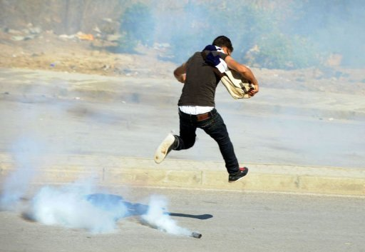 <p>A Tunisian protester runs for cover from tear gas fired by riot police during a demonstration against a film mocking Islam in Tunis on September 14. Washington said it was deploying forces to cope with violence in as many as 18 different locations as deadly Muslim anger spreads.</p>