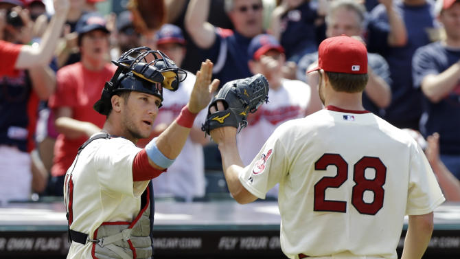 Cleveland Indians catcher Yan Gomes, left, greets starting pitcher Corey Kluber (28) after Kluber got out of a bases-loaded jam against the Washington Nationals in the seventh inning of a baseball game on Sunday, June 16, 2013, in Cleveland. (AP Photo/Mark Duncan)
