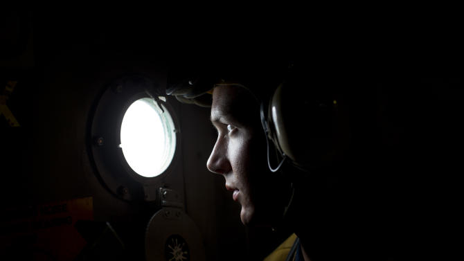 In this Oct. 16, 2012 photo, Boatswain's Mate 3 Billy Lewis, from Trenton, Tennessee, watches a helicopter land on the flight deck from the window of a hatch door onboard the USS Underwood while patrolling in international waters near Panama.  In October, the 30-year-old ship was patrolling the Caribbean waters off Panama, as part of a multi-national effort to hit illicit trafficking routes on both coasts of the Central American isthmus. The deployment was the Underwood's last voyage, with 10 other U.S. Navy ships scheduled to be decommissioned early next year. (AP Photo/Dario Lopez-Mills)