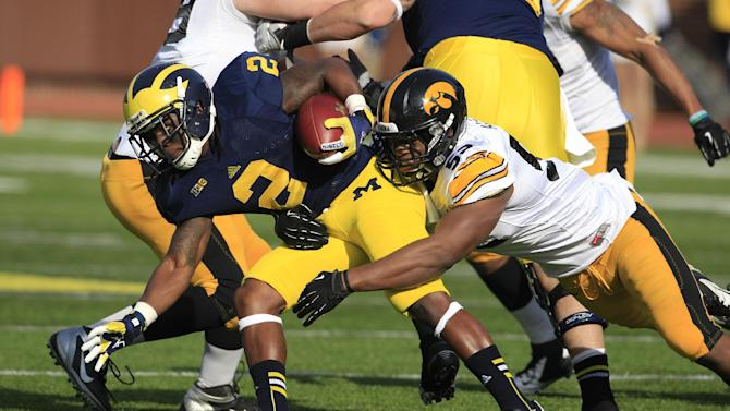 Michigan running back Vincent Smith (2) is stopped by Iowa linebacker Quinton Alston (52) during the first quarter of an NCAA college football game at Michigan Stadium in Ann Arbor, Mich., Saturday, Nov. 17, 2012. (AP Photo/Carlos Osorio)