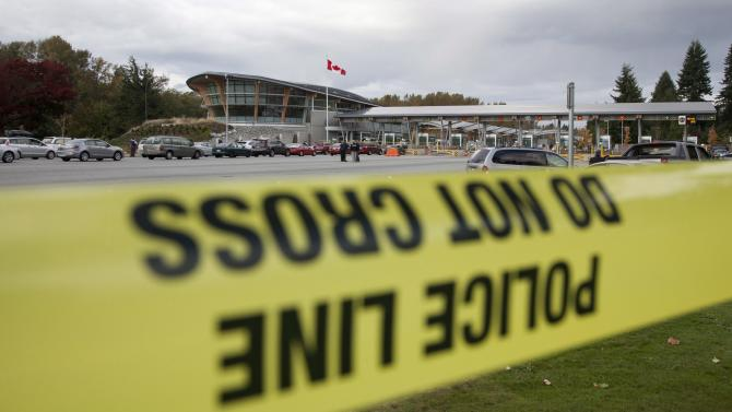 Police officers investigate the scene of a shooting at the Blaine, Wash./Surrey, British Columbia border crossing, Tuesday, Oct. 16, 2012, in Surrey. Royal Canadian Mounted Police Cpl. Bert Paquet says a border officer was in her booth when she was shot in the neck at about 2 p.m. Tuesday by a man trying to enter Canada in a van with Washington state plates. (AP Photo/The Canadian Press, Jonathan Hayward)