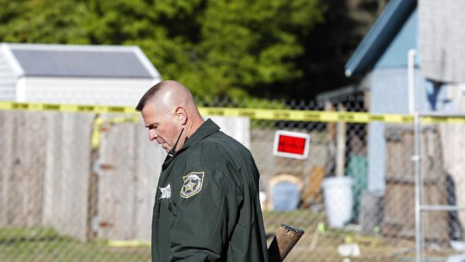 Hillsborough Sheriff Deputy removes two rifles that were recovered from the home of Jeff Bush,  as it is destroyed, Monday, March 4, 2013 in Seffner, Fla.  A sinkhole opened up underneath the house late Thursday, Feb. 28, 2013, swallowing Bush, 37.  The 20-foot-wide opening of the sinkhole was almost covered by the house, and rescuers said there were no signs of life since the hole opened Thursday night.  (AP Photo/Scott Iskowitz)