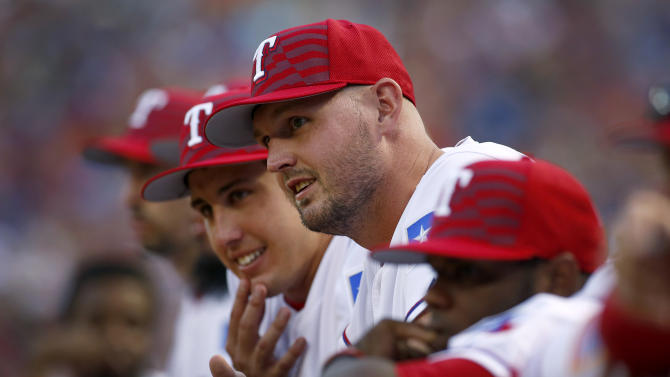 Texas Rangers pitcher Matt Harrison, middle, watches the team's baseball game against the Los Angeles Angels from the dugout in Arlington, Texas, on Saturday, July 4, 2015. Next to Harrison, to the rear, is Derek Holland. (AP Photo/Brad Loper)