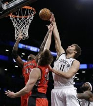 Brooklyn Nets center Brook Lopez (11) shoots over the defense of Toronto Raptors forward Ed Davis (32) and center Aaron Gray (34) in the first half of an NBA basketball game Tuesday, Jan. 15, 2013, in New York. (AP Photo/Kathy Willens)