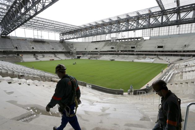 Workers walk inside the Arena da Baixada soccer stadium as it is being built to host matches of the 2014 World Cup in Curitiba