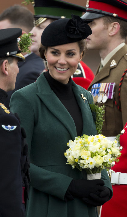 Britain's Kate the Duchess of Cambridge holds flowers after presenting traditional sprigs of shamrocks to members of the 1st Battalion Irish Guards at the St Patrick's Day Parade at Mons Barracks in A