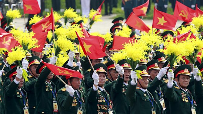 Veterans wave communist and Vietnamese national flag during a parade marking Vietnam's 70th National Day at Ba Dinh square in Hanoi, Vietnam