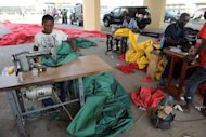 <p>Tailors make flags, January 6, 2013, in Accra ahead of the inauguration of President John Dramani Mahama. Ghana's president will be sworn into office on Monday following last month's polls in a ceremony to be boycotted by the opposition, which has claimed fraud and challenged the results in court</p>