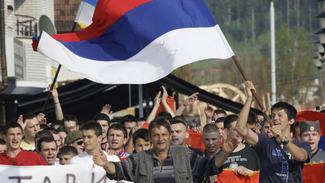 """Bosnian Serb people wave Serbian flags and chant slogans with banner (partially seen at left) reading """"Genaral, we are with you""""  to support Gen. Ratko Mladic, in war time stronghold Pale, 20 kms from Sarajevo, Bosnia, on Friday, May 27 2011. More than 2000 people gathered and marched along the streets to give their support to Gen. Ratko Mladic, who has been arrested on charges relating to alleged war crimes thought to have been committed by him during the Bosnian 1992-95 war. (AP Photo/Amel Emric)"""