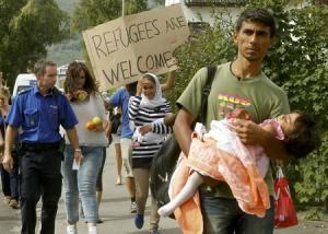 A Swiss police officer accompanies migrants from Syria…