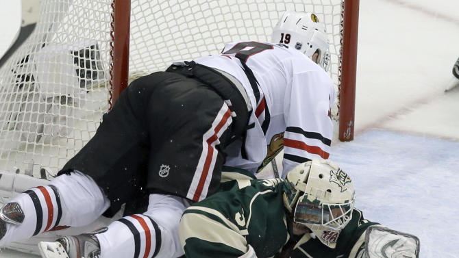 Chicago Blackhawks' Jonathan Toews, left, falls on Minnesota Wild goalie Josh Harding as Harding stoped a shot by Toews in the first period of Game 4 of an NHL hockey Stanley Cup playoff series, Tuesday, May 7, 2013 in St. Paul, Minn. Harding was injured on the play and left the game after the first period. (AP Photo/Jim Mone)
