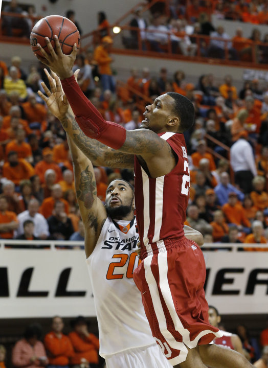 Oklahoma forward Romero Osby (24) goes up for a shot in front of Oklahoma State forward Michael Cobbins (20) in the second half of an NCAA college basketball game in Stillwater, Okla., Saturday, Feb.