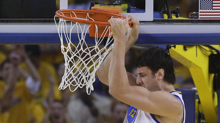 Golden State Warriors center Andrew Bogut, from Australia, right, dunks over San Antonio Spurs forward Tim Duncan (21) during the first quarter of Game 3 of a Western Conference semifinal NBA basketball playoff series in Oakland, Calif., Friday, May 10, 2013. (AP Photo/Jeff Chiu)