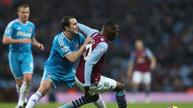 Sunderland's John O'Shea, left, and Aston Villa's Christian Benteke battle for the ball during their English Premier League soccer match at Villa Park, Birmingham, England, Sunday, Dec. 28, 2014. (AP Photo/David Davies, PA Wire)      UNITED KINGDOM OUT    -   NO SALES    -    NO ARCHIVES