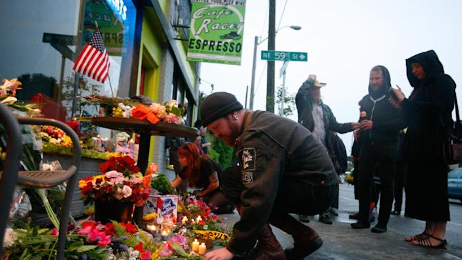 In this Wednesday, May 30, 2012 photo, mourners place flowers and candles in front of Cafe Racer in Seattle, where a gunman killed four people earlier in the day. The gunman then killed a fifth person in a carjacking before he apparently shot himself as officers closed in following a citywide manhunt. (AP Photo/seattlepi.com, Sofia Jaramillo)  MAGS OUT; NO SALES; SEATTLE TIMES OUT; TV OUT; MANDATORY CREDIT