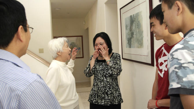 Phan Thi Kim Phuc, center right, wipes her eyes as she introduces Dr. My Le, who treated Kim Phuc in Vietnam two days after a napalm attack in Vietnam on June 8, 1972, to her two sons, Thomas, second from right, and Stephen Bui, right, during a reunion in Buena Park, Calif. on Saturday, June 2, 2012. It only took a second for Associated Press photographer Nick Ut to snap the iconic black-and-white image of her after the attack 40 years ago. It communicated the horrors of the Vietnam War in a way words could never describe, helping to end one of America's darkest eras. But beneath the photo lies a lesser-known story. It's the tale of a dying child brought together by chance with a young photographer. A moment captured in the chaos of war that would serve as both her savior and her curse on a journey to understand life's plan for her. (AP Photo/Jae C. Hong)
