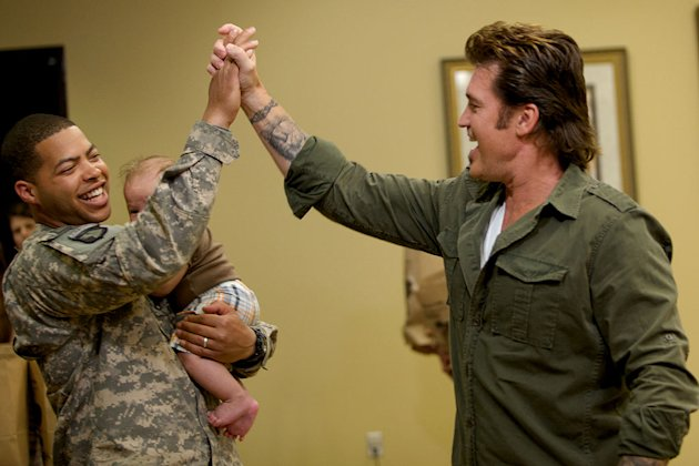 "Staff Sargeant Jonathan Bentley holds baby while he high fives Billy Ray Cyrus upon his return as seen on ""Surprise Homecoming."""