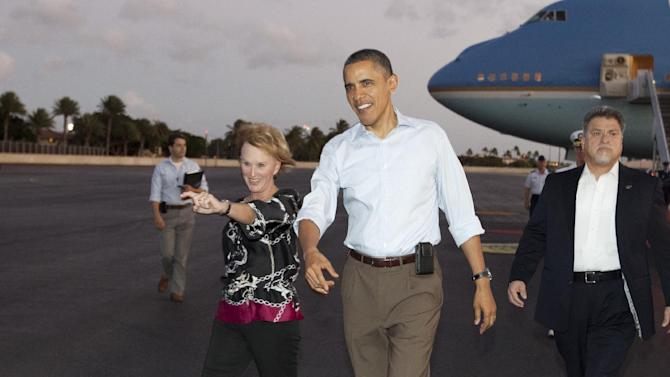 President Barack Obama walks with Donna Willard, wife of Admiral Robert Willard, to greet people waiting for him on the tarmac as he arrives on Air Force One at Hickam Air Force Base in Friday, Dec. 23, 2011, in Honolulu. (AP Photo/Carolyn Kaster)