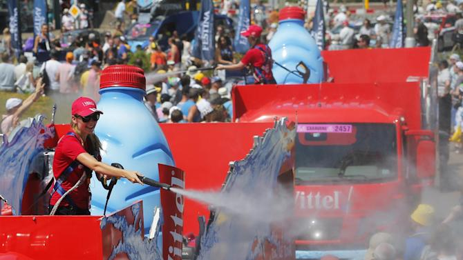 The publicity caravan sprays water on spectators as they wait for the start of the first stage of the Tour de France cycling race, an individual time trial over 13.8 kilometers (8.57 miles), with start and Finish in Utrecht, Netherlands, Saturday, July 4, 2015. Temperatures rose to 36 degrees Celsius or 97 degrees Fahrenheit around noon. (AP Photo/Christophe Ena)