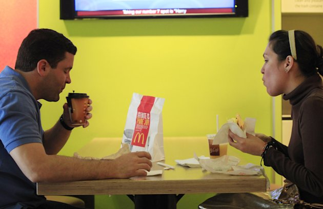 "Carlos Gonzalez and Elsa Guzman eat breakfast at a McDonald's restaurant, Wednesday, Sept. 12, 2012 in New York. McDonald's restaurants across the country will soon get a new menu addition: The number of calories in the chain's burgers and fries. The world's biggest hamburger chain said Wednesday that it will post calorie information on restaurant and drive-thru menus nationwide starting Monday. The move comes ahead of a regulation that could require major chains to post the information as early as next year. ""It's good to know the calories I'm consuming so I can plan out my whole day,"" said Gonzalez. (AP Photo/Mark Lennihan)"