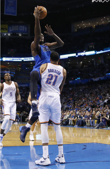 Dallas Mavericks center Samuel Dalembert (1) commits an offensive foul as he shoots over Oklahoma City Thunder forward Andre Roberson (21) in the first quarter of an NBA basketball game in Oklahoma Ci