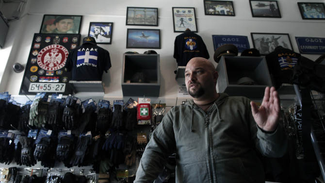 In this Oct. 26, 2012, photo, extreme far-right Golden Dawn party lawmaker Ilias Panagiotaros speaks in his shop in central Athens, explaining his party's policies and rejects accusations that it has been involved in racist attacks in Greece. Human rights and immigrant groups say there has been an increase in racist attacks in Greece over the last year, as the country struggles through a protracted financial crisis. On the top left a picture of Serbian warlord Zeljko Raznatovic Arkan is displayed.(AP Photo/Petros Giannakouris)