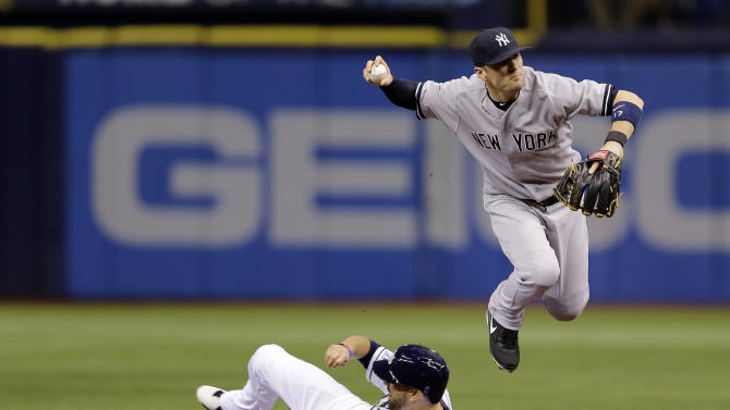 New York Yankees second baseman Brendan Ryan leaps over Tampa Bay Rays' David DeJesus after forcing him at second base on a fielder's choice by Evan Longoria during the first inning of a baseball game Tuesday, Sept. 16, 2014, in St. Petersburg, Fla. (AP Photo/Chris O'Meara)