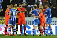 Bolton Wanderers' Jay Spearing restrains Wigan Athletic's Ivan Ramis from confronting Neil Danns (centre left)