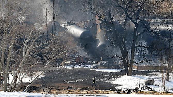 FILE - In this Feb. 17, 2015 file photo, crew members walk near the scene of a train derailment near Mount Carbon, W.Va. A CSX train carrying more than 100 tankers of crude oil derailed in a snowstorm, sending a fireball into the sky. Fiery wrecks this month of trains hauling crude oil have intensified pressure on the Obama administration to approve tougher standards for railroads and tank cars despite industry complaints that it could cost billions and slow freight deliveries. (AP Photo/Chris Tilley, File)