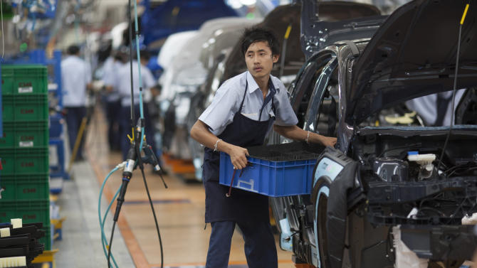 Thai Ford Manufacturing employees work on an assembly line Friday, Aug. 31, 2012, at the Ford Motor Company factory in Rayong, Thailand.   Ford held a ceremony at the new factory on Friday to announce the 350 millionth Ford Focus globally produced.  (AP Photo/str)