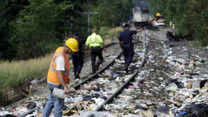 Officials survey the scene where an Amtrak train smashed into a tractor-trailer, Monday, July 11, 2011, in North Berwick, Maine. Officials say the truck driver was killed and some of the train's 109 passengers were injured.  The crash happened at about 11 a.m. in North Berwick, about 40 miles south of Portland. (AP Photo/Pat Wellenbach)