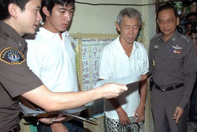 In this photo taken Aug. 3, 2010, Amphon Tangnoppakul, second right, is arrested by Thai police officers of defaming Thailand's royal family in mobile phone text messages at his house in Bangkok, Thai