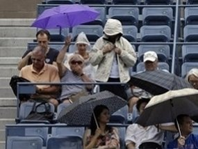 Spectators sit under umbrellas during a rain delay at the 2012 US Open tennis tournament,  Wednesday, Sept. 5, 2012, in New York. (AP Photo/Darron Cummings)