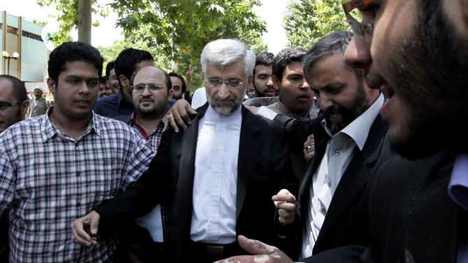 Iranian presidential candidate Saeed Jalili, center, Iran's top nuclear negotiator, leaves after a campaign rally, at the Tehran University, in Iran, Monday, June 3, 2013. The presidential election will be held on June 14. (AP Photo/Vahid Salemi)