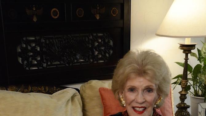 "In this November 3, 2011 photo, pioneering meditation teacher and author, Nancy Cooke de Herrera, is seen in her home in Beverly Hills, Calif. She holds the cover of a Swedish publication, ""Vecko-Journalen"" that  features her as the Ambassadress of Fashion during a professional tour to Sweden in 1957. She died Feb. 28, 2013 at 90 in Los Angeles. (AP Photo/Pamela Hassell)"