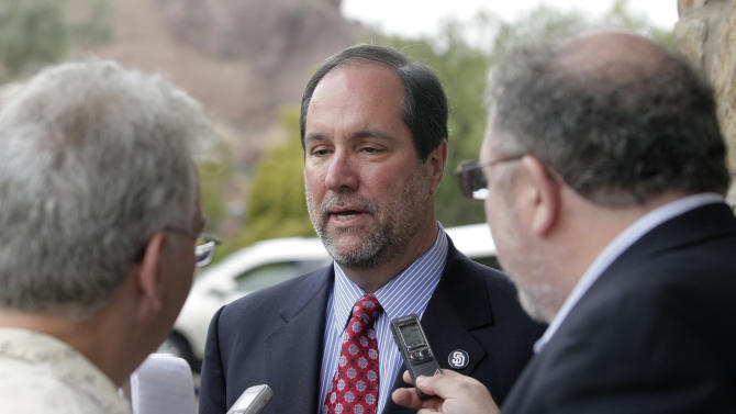 San Diego Padres CEO Jeff Moorad, center, answers reporters' questions at a baseball owners meeting Thursday, Jan. 12, 2012, in Paradise Valley, Ariz. Owners deferred a vote on the proposed transfer of the San Diego Padres from John Moores to Jeff Moorad, saying they needed more financial information. (AP Photo/Paul Connors)