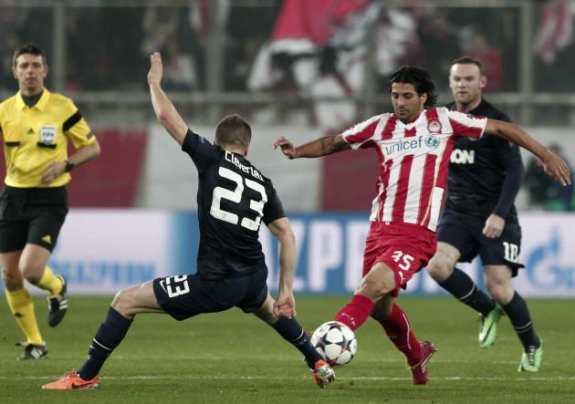 Olympiakos' Dominguez challenges Manchester United's Cleverley during their Champions League round of 16 first leg soccer match at Karaiskaki stadium in Piraeus, near Athens