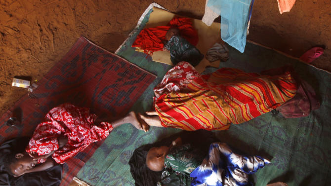 In this photograph taken Sunday Aug. 7, 2011,  A Somali refugee whose identity is being withheld to protect her as a rape victim, lays in her hut with her children at the Ifo refugee camp outside  Dadaab, Eastern Kenya, 100 kms (60 miles) from the Somali border. speaking to AP, she said she was gang-raped by five men after a group of families traveling together were ambushed. Sexual attacks against famine refugees from Somalis fleeing to Kenya are rising dramatically, but Kenyan police say they don't have enough manpower to stop the attacks. That lack of manpower underscores a larger problem for Kenya: Officials here say they are being overwhelmed by the influx of tens of thousands of Somali refugees, and they're letting U.S., U.N. and other world leaders know about it.  (AP Photo/Jerome Delay)